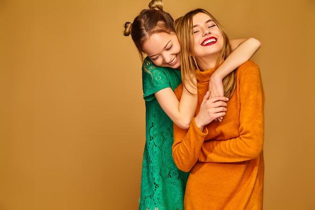 Беззаботные женщины, изолированные на золотой стене позитивные модели позируют со своими платьями