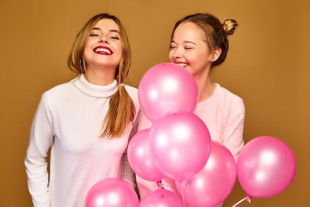 Женские модели с розовыми воздушными шариками на золотой стене