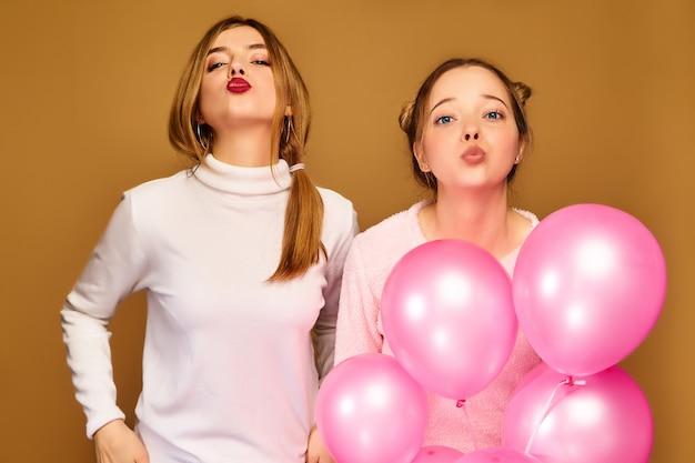 黄金の壁にピンクの気球を持つ女性モデル