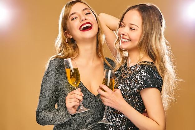 金色の壁にシャンパングラスとスタイリッシュな魅力的なドレスで幸せな笑顔の女性