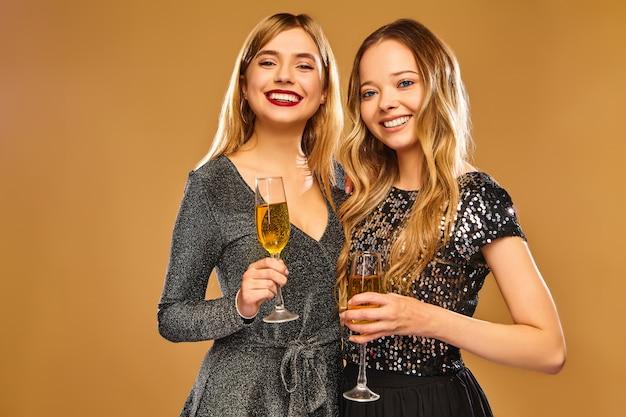 Счастливые улыбающиеся женщины в стильных гламурных платьях с бокалами шампанского на золотой стене