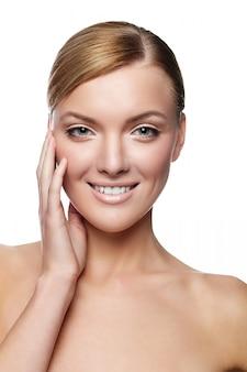 健康な顔ときれいな肌と美しい若い笑顔の女性