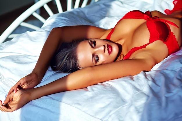 Женская модель носить красное белье на кровати по утрам