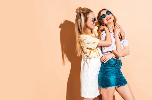 Две молодые красивые улыбающиеся белокурые хипстерские девочки в модной летней красочной футболке одеваются.