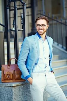 茶色の袋が付いている通りでスーツを着ているビジネスマン