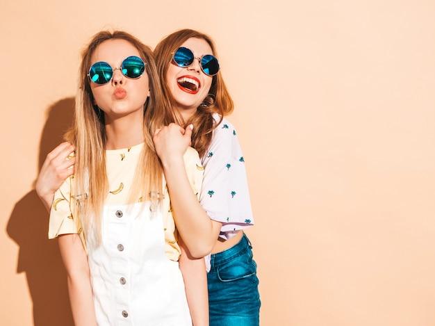 Две молодые красивые улыбающиеся белокурые хипстерские девочки в модной летней красочной футболке одеваются. и дает воздушный поцелуй