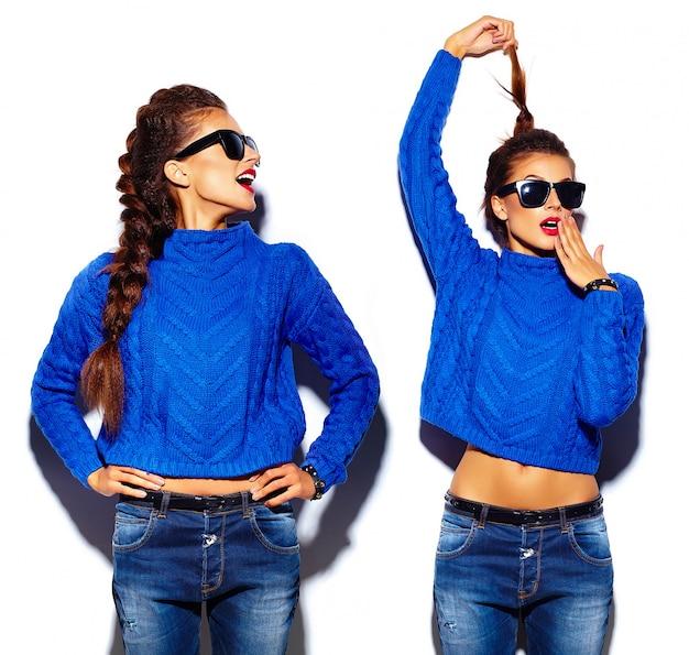 赤い唇とサングラスの青いセーターを持つ若い女性