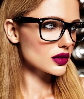 紫色の唇の色とメガネできれいな健康的な肌と新鮮な毎日のメイクと美しい金髪の女性モデルの官能的な魅力の肖像画