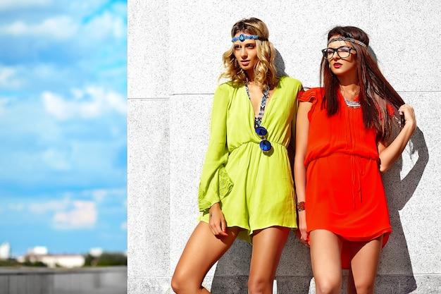Фасонируйте портрет двух молодых моделей хиппи женщин в солнечный летний день в яркой красочной одежде битник