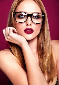 暗い唇の色とメガネの赤の背景にきれいな健康的な肌と新鮮な毎日のメイクとホット金髪美人モデル