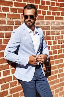 通りの背景にレンガの壁に近いポーズエレガントな青いスーツに身を包んだセクシーなハンサムなファッションビジネスマンモデルの肖像画。メトロセクシャル