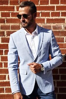 Портрет сексуальной красивой модели бизнесмена модели одел в изящном синем костюме, позирующем около кирпичной стены на фоне улицы. метросексуал