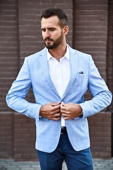通りの背景にポーズをとってエレガントな青いスーツに身を包んだセクシーなハンサムなファッションビジネスマンモデルの肖像画。メトロセクシャル
