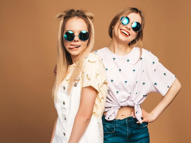 Две молодые красивые улыбающиеся белокурые хипстерские девушки в модной летней красочной футболке одевают