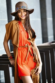 夏の明るい流行に敏感な服で面白いスタイリッシュなセクシーな笑みを浮かべて美しい若いヒッピー女性モデルのドレスは帽子の通り