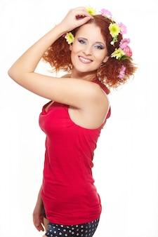 Портрет красивые улыбающиеся рыжая рыжая женщина в красной ткани с желтыми розовыми красочными цветами в волосах, изолированных на белом