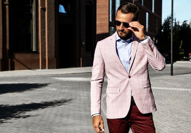 通りの背景にポーズをとってエレガントなスーツに身を包んだセクシーなハンサムなファッションビジネスマンモデルの肖像画。メトロセクシャル