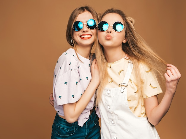 Две молодые красивые улыбающиеся белокурые хипстерские девочки в модной летней красочной футболке одеваются. сексуальные беззаботные женщины позируют на бежевом фоне в круглых очках. веселые позитивные модели