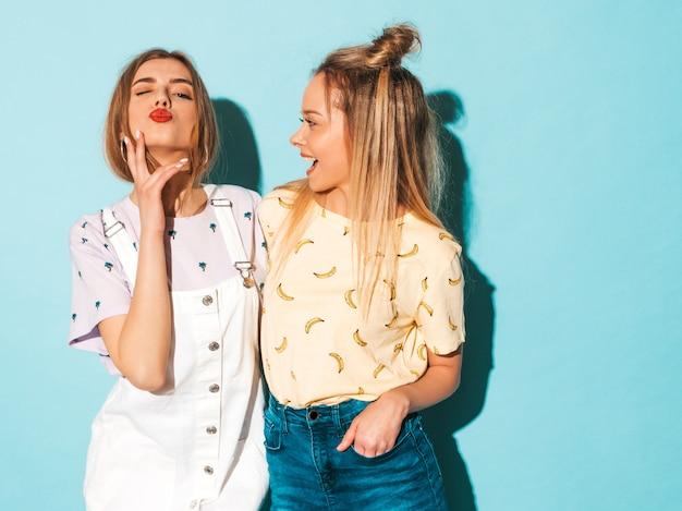 Две молодые красивые улыбающиеся белокурые хипстерские девочки в модной летней красочной футболке одеваются. и дает поцелуй
