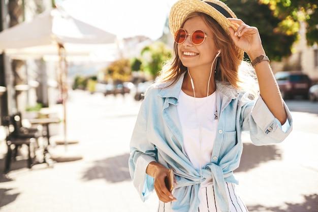 通りでポーズをとって夏服の金髪モデル