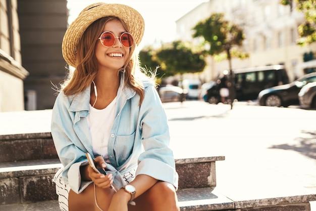 音楽を聴く路上でポーズをとって夏服の金髪モデル