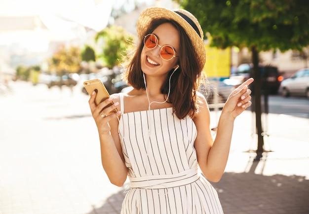 Брюнетка модель в летней одежде позирует на улице с помощью мобильного телефона