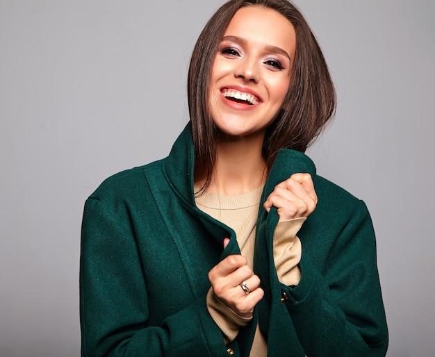 Улыбается милая брюнетка женщина в повседневной зеленой куртке на сером
