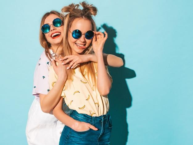 Две молодые красивые улыбающиеся белокурые хипстерские девочки в модной летней красочной футболке одеваются. и показывая язык