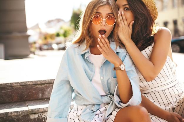Молодые стильные девушки позируют на улице