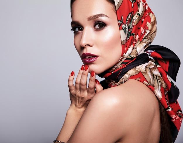 Деловая женщина в черном платье с вечерним макияжем и красочными губами в красной шали
