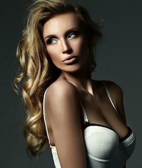 新鮮な化粧と健康的な巻き毛の美しい金髪の女性モデルの女性の官能的な魅力の肖像画