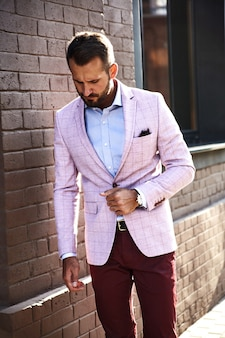 通りの背景にレンガの壁に近いポーズのエレガントなスーツに身を包んだセクシーなハンサムなファッションビジネスマンモデルの肖像画。メトロセクシャル