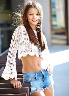 Смешные стильные сексуальные улыбающиеся красивые молодые хиппи женщина модель в летних белых одеждах битник позирует на улице