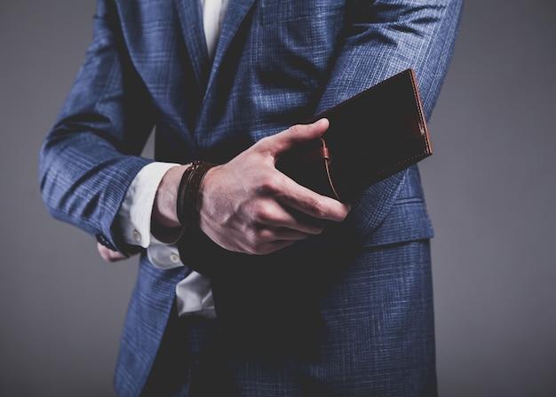 灰色のエレガントな青いスーツに身を包んだ青年実業家ハンサムなモデル男のファッションの肖像画。
