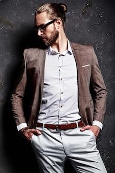 Портрет красивого модного стильного хипстерского бизнесмена, одетого в элегантный коричневый костюм в очках у темной стены