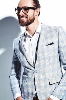 Портрет красивый модный стильный битник бизнесмен модель одет в элегантный светло синий костюм в очках на белом.