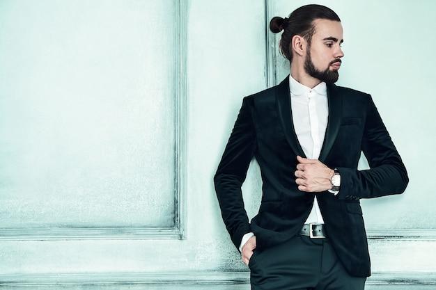 Портрет красивый модный стильный битник бизнесмен модель, одетый в элегантный черный костюм.