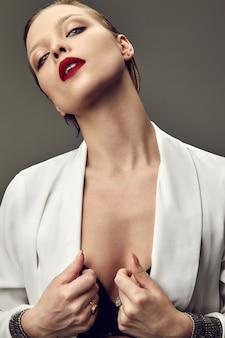 夜のメイクと白いジャケットに赤い唇と美しいファッションスタイリッシュなブルネットの女性モデルの肖像画