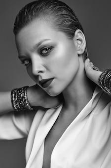 Портрет красивой модной стильной модели брюнетки с вечерним макияжем и красными губами в белой куртке