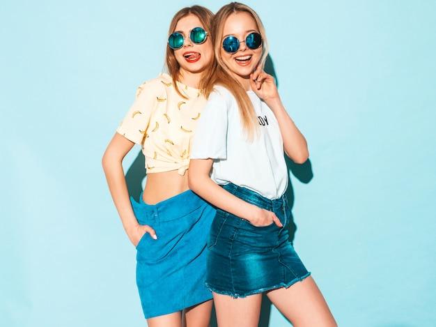 Две молодые красивые улыбающиеся блондинка битник девушки в модных летних джинсах юбки одежды.