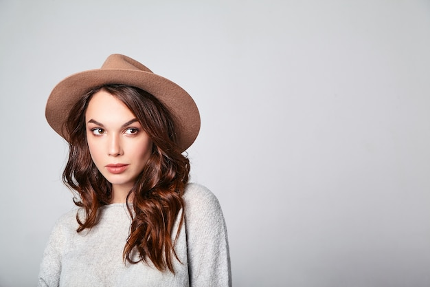 自然化粧品で茶色の帽子で灰色のカジュアルな夏服で若いスタイリッシュな笑いモデルの肖像