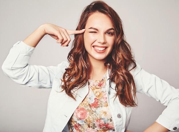 Портрет молодой стильной смеющейся модели в разноцветной повседневной летней одежде с естественным макияжем на сером