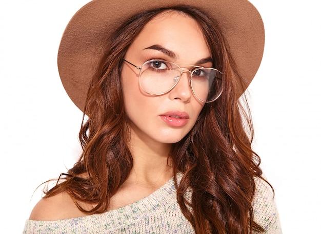 Портрет молодой стильной модели в повседневной летней одежде в коричневой шляпе с естественным макияжем в очках на белом
