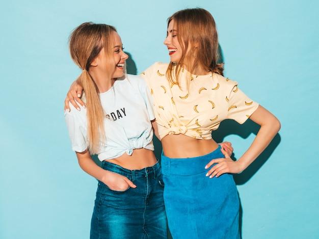 Две молодые красивые улыбающиеся белокурые хипстерские девочки в модной летней красочной футболке одеваются. сексуальные беззаботные женщины позируют возле синей стены. позитивные модели смотрят друг на друга