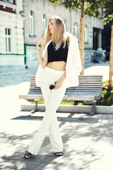 通りの背景にポーズをとって白いスーツでセクシーなファッションモダンな実業家モデルの肖像画