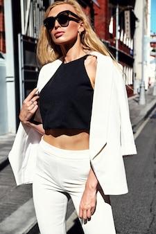 通りの背景にポーズをとって白いスーツでセクシーなファッションモダンな実業家モデルの肖像画。歩く