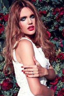 Портрет красоты очарования красивой чувственной кавказской модели молодой женщины с вечерней косметикой в белом летнем платье, позирующем на уличном фоне около цветочного фона