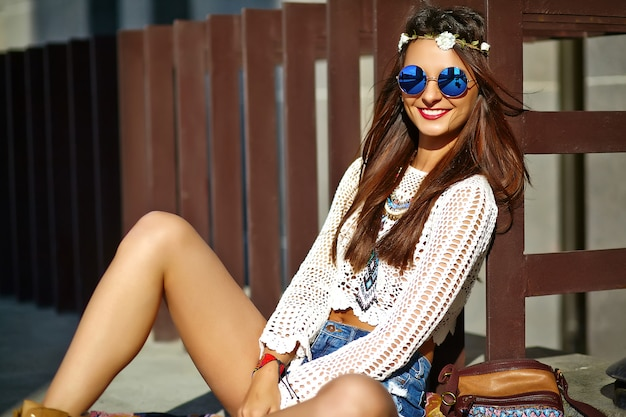 通りでポーズをとって夏白いヒップスター服で面白いスタイリッシュなセクシーな笑顔美しい若いヒッピー女性モデル