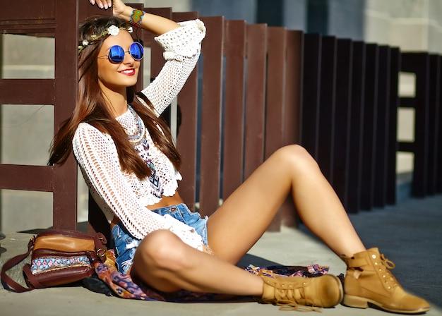 Смешная стильная сексуальная улыбающаяся красивая молодая хиппи женщина модель в летних белых одеждах битник позирует на улице