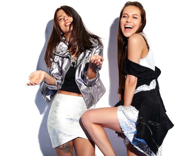 Портрет двух улыбающихся брюнеток в летней повседневной хипстерской одежде на белом